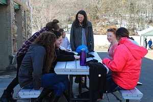 Group of teens around a picnic table in the winter talking.
